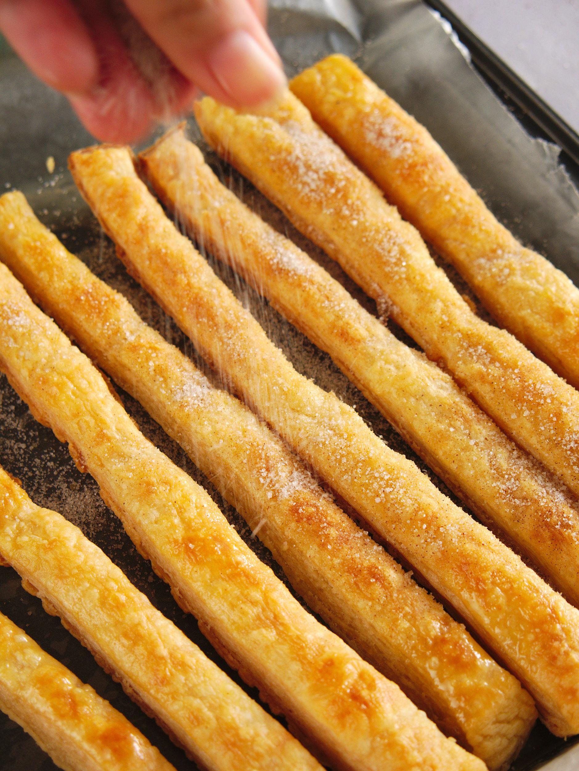 dusting baked churros with cinnamon sugar